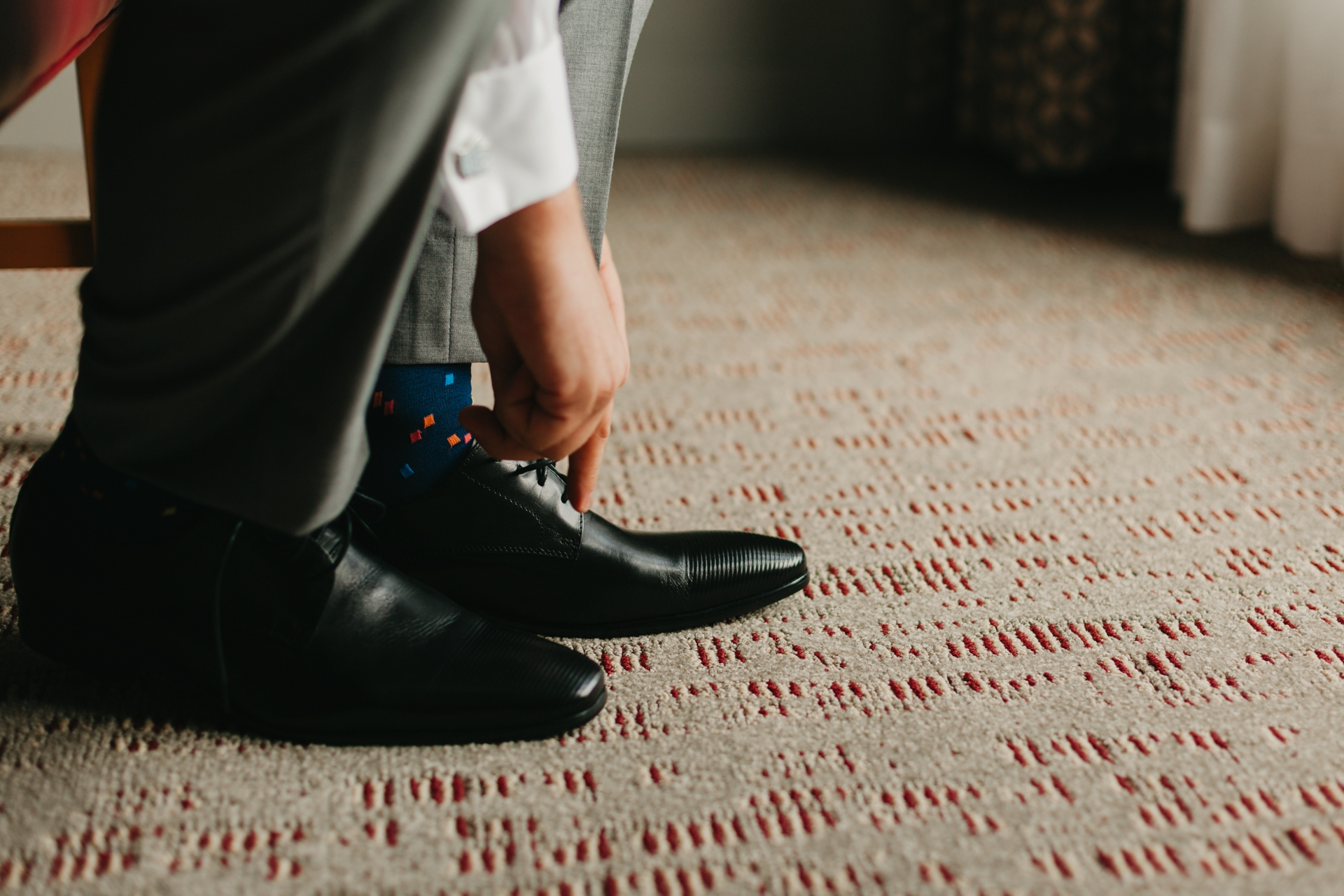 photo of the groom tying his shoe