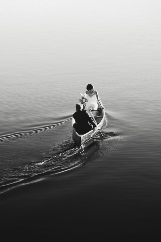Bride and Groom in a canoe on the Ottawa River on wedding day, going to surprise their guests. Black and White image