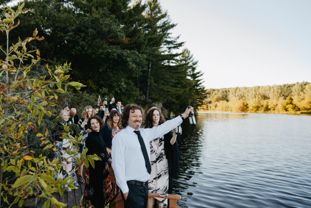 Guests celebrating the surprise arrival of the bride and groom pulling up in a canoe.